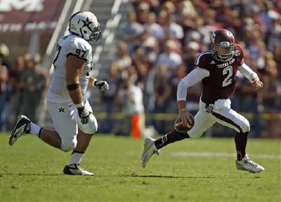 Texas A&M's Johnny Manziel, right, avoids the tackle of Vanderbilt's Jared Morse during the second half of an NCAA football game, Saturday, Oct. 26, 2013, in College Station, Texas. (AP Photo/Eric Christian Smith) Photo: AP / FR171023 AP