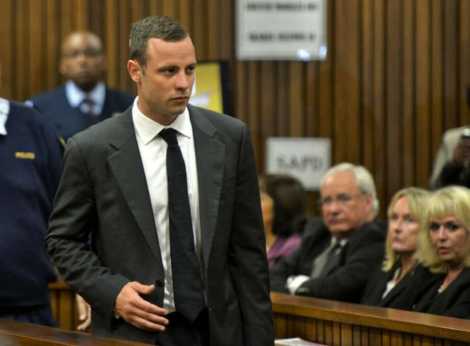 Oscar Pistorius is watched by June Steenkamp, 2nd right, the mother of Reeva Steenkamp, as he arrives for his trial at the high court in Pretoria, South Africa, Monday, March 3, 2014. Pistorius is charged with murder with premeditation in the shooting death of girlfriend Reeva Steenkamp in the pre-dawn hours of Valentine's Day 2013. (AP Photo/Herman Verwey, Media24- Pool) Photo: AP / POOL MEDIA 24