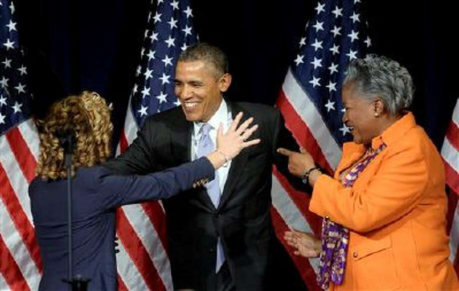 President Barack Obama, center, goes to give Democratic National Committee Chairwoman Rep. Debbie Wasserman-Schultz, D-Fla., left, a hug as Democratic strategist Donna Brazile watches at right, as Obama arrived to speak at the Democratic National Committee Winter Meeting in Washington, Friday, Feb. 28, 2014. (AP Photo/Susan Walsh) Photo: AP / AP