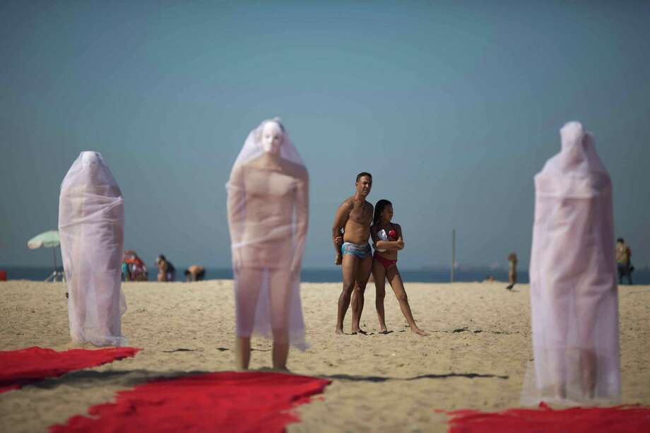 Beachgoers look at a trio of veiled wrapped mannequins that are part of a a protest staged by Rio de Paz activists on Copacabana beach to press for clarifications on missing persons including a bricklayer who recently disappeared, in Rio de Janeiro, Brazil, Wednesday, July 31, 2013. The 42-year-old father of six was picked up for police questioning on suspicions of involvement in drug trafficking, but was released shortly thereafter. He has not been seen from since. The Rio de Paz civic organization cites official statistics showing that nearly 35,000 people were reported as missing in Rio state alone over the past five years. (AP Photo/Felipe Dana) Photo: AP / AP2013