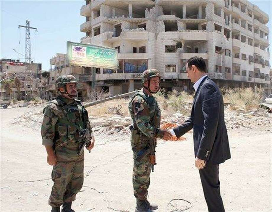 This image posted on the official Facebook page of the Syrian Presidency on Thursday, Aug. 1, 2013 purports to show Syrian President Bashar Assad shaking hands with a solider during Syrian Arab Army day in Darya, Syria. Syrian state-run TV says Assad has visited a tense Damascus suburb to inspect his troops on the occasion of the country's Army Day. The visit on Thursday is Assad's first known public trip outside the capital, his seat of power, since he visited the Baba Amr district in the central city of Homs after troops seized it from rebels in March 2012. Daraya, just south of Damascus, was held by rebels for a long time and it took the army weeks of heavy fighting to regain control earlier this year. (AP Photo/Syrian Presidency via Facebook) Photo: AP / Syrian Presidency via Facebook