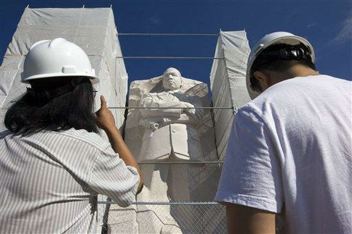 FILE - In this July 29, 2013 file photo, sculptor Master Lei Yixin, left, surveys the Martin Luther King Jr. Memorial in Washington. Sculptor Lei Yixin says he has removed a disputed inscription from the Martin Luther King Jr. Memorial on the National Mall, and he is now working on a new finish for the side of the memorial statue. Plans call for Lei to carve grooves over the former words to match existing striation marks in the King memorial. Lei said Thursday he is working to deepen all of the grooves so that they will match. (AP Photo/Jacquelyn Martin, File)