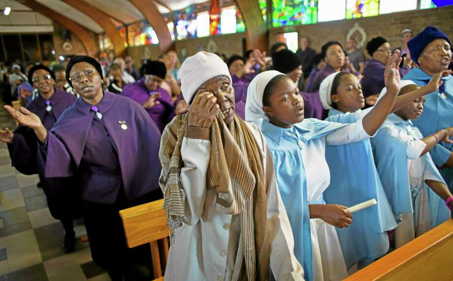 A mourner wipes away a tear at a morning mass in memory of Nelson Mandela at the Regina Mundi church, which became one of the focal points of the anti-apartheid struggle, in Soweto, Johannesburg, South Africa Sunday, Dec. 8, 2013. South Africans flocked to houses of worship Sunday for a national day of prayer and reflection to honor Nelson Mandela, starting planned events that will culminate in what is expected to be one of the biggest funerals in modern times. (AP Photo/Ben Curtis) Photo: AP / AP