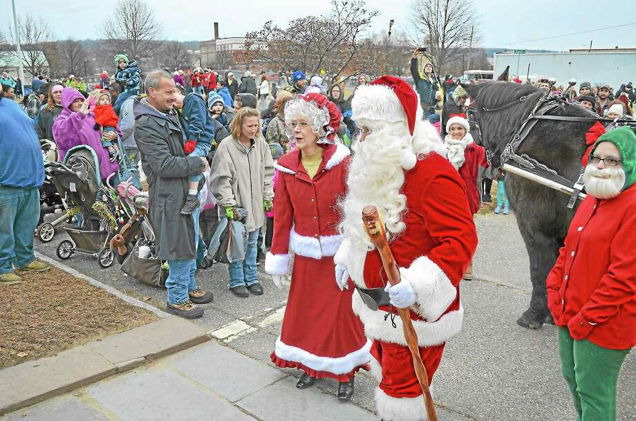 Santa and Mrs. Claus arrive at Christmas Village in Torrington Sunday at the end of the annual parade to open the holiday attraction. Photo: John Berry - Register Citizen