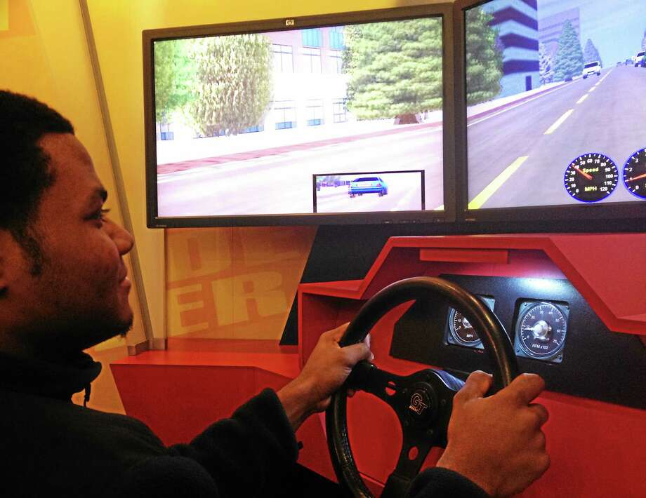 Isaac Avilucea - Register Citizen Stanly Pilier, a senior at Torrington High School, drives a distracted driving simulator Monday during a presentation at the school. Photo: Journal Register Co.