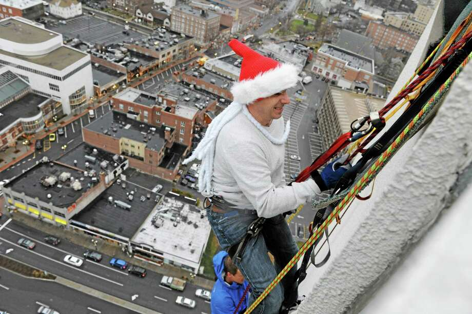 New York Yankees general manager Brian Cashman rappels down One Landmark Square during a charity event on Friday in Stamford. Register sports columnist Chip Malafronte appreciates that Cashman has spent $283 million on Jacoby Ellsbury, Brian McCann and Hiroki Kuroda, but is quick to point there are about five or six other pinstriped holes to fill. Photo: Dru Nadler — The Stamford Advocate  / The Stamford Advocate