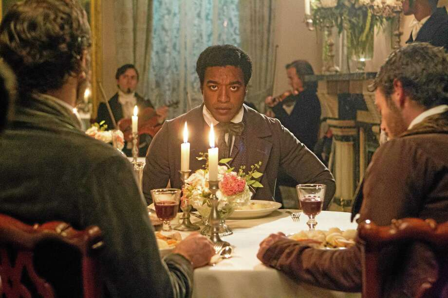 """This film publicity image released by Fox Searchlight shows Chiwetel Ejiofor in a scene from """"12 Years A Slave."""" This year's best picture race at the 86th Academy Awards on Sunday, March 2, 2014, has shaped up to be one of the most unpredictable in years. The favorites are """"12 Years a Slave,"""" """"Gravity"""" and """"American Hustle."""" (AP Photo/Fox Searchlight Films, Jaap Buitendijk, file) Photo: AP / Fox Searchlight"""