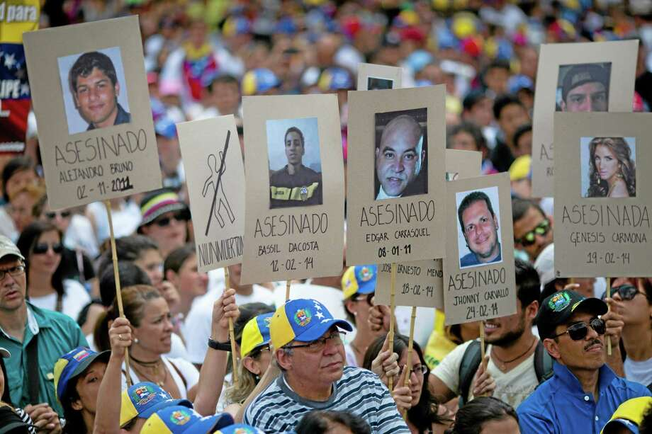 Demonstrators hold up posters with images of Venezuelans who were killed in the past two weeks during the recent unrest, at a rally with human rights activists in Caracas, Venezuela, Friday, Feb. 28, 2014. The start of a weeklong string of holidays leading up to the March 5 anniversary of former President Hugo Chavez's death has not completely pulled demonstrators from the streets as the government apparently hoped. President Nicolas Maduro announced this week that he was adding Thursday and Friday to the already scheduled long Carnival weekend that includes Monday and Tuesday off, and many people interpreted it as an attempt to calm tensions. (AP Photo/Rodrigo Abd) Photo: AP / AP