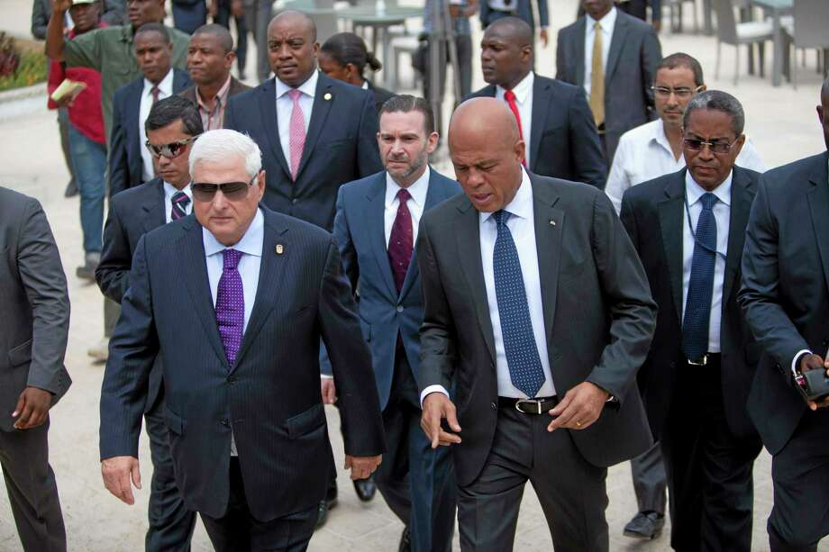 Haitian president Michel Martelly, right, walks with Panama's President Ricardo Martinelli, left, after a joint press conference in Petion-Ville, Haiti, Wednesday Feb. 19, 2014. Panamanian President Ricardo Martinelli arrived in Haiti as part of an effort to promote business between the two countries that have not traditionally had strong ties. (AP Photo/Dieu Nalio Chery) Photo: AP / AP