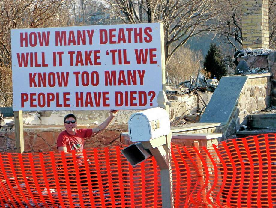 This Jan. 17, 2013 photo provided by Paul Libera shows him with the sign he raised in his yard in Webster, N.Y., a few weeks after a gunman shot and killed two firefighters in the town and after the Dec. 14, 2012 massacre at Sandy Hook Elementary School in Newtown, Conn. His idea was to get people to reconsider old attitudes about guns, but many people were angered by the sign in an area with an active and vocal community of gun owners. Libera has stowed the sign in his garage, but hopes it's gotten some people to think. (AP Photo/Courtsey of Paul Libera) Photo: AP / Paul Libera