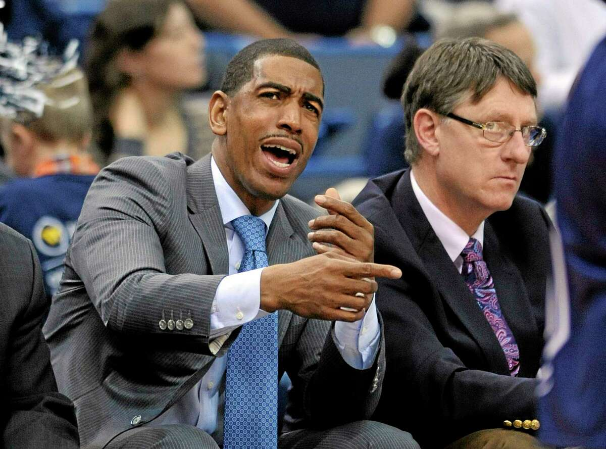 UConn coach Kevin Ollie signals to his team as associate head coach Glenn Miller looks on during the first half of the 12th-ranked Huskies' 95-68 victory over Maine on Friday night at the XL Center in Hartford.