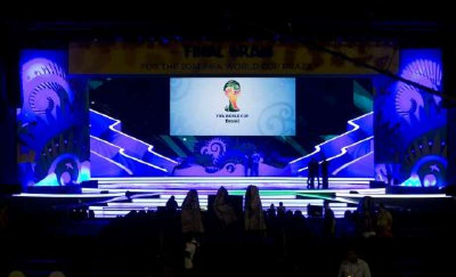 Workers stand on the stage where the 2014 soccer World Cup draw will take place in Costa do Sauipe, Brazil, Thursday, Dec. 5, 2013.