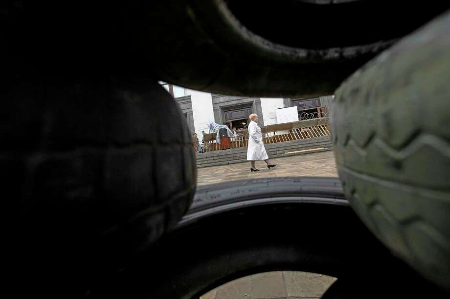 A woman passes barricades of tires in front of a government office seized Tuesday,  Luhansk, one of the largest cities in eastern, Ukraine, Wednesday, April 30, 2014. Pro-Russian gunmen have seized more administrative buildings in eastern Ukraine, further raising tensions in Ukraine's Russian-leaning regions shaken by separatist unrest.(AP Photo/Alexander Zemlianichenko) Photo: AP / AP