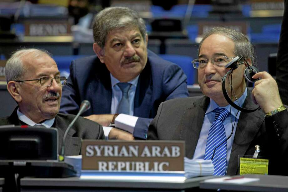 Dr. Faisel Mekdad of the Syrian Arab Republic, right, and fellow delegation members wait for the start of the eighteenth session of the Conference of the States Parties of the Organisation for the Prohibition of Chemical Weapons (OPCW) in The Hague, Netherlands, Monday, Dec. 2, 2013. The world's chemical weapons watchdog is expected to discuss its ambitious plan to completely eradicate Syria's chemical weapons program by mid-2014. (AP Photo/Peter Dejong) Photo: AP / AP