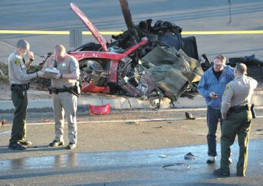 """Sheriff's deputies work near the wreckage of a Porsche that crashed into a light pole on Hercules Street near Kelly Johnson Parkway in Valencia, Calif., on Nov. 30, 2013. A publicist for actor Paul Walker says the star of the """"Fast & Furious"""" movie series died in the crash. He was 40."""