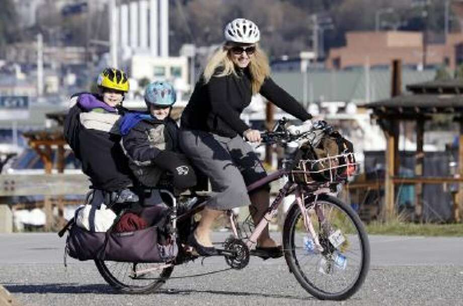 Madi Carlson pedals as her sons Rijder, 4, left, and Brandt, 6, ride aboard the family cargo bike as they head to an after-school gym program in Seattle.