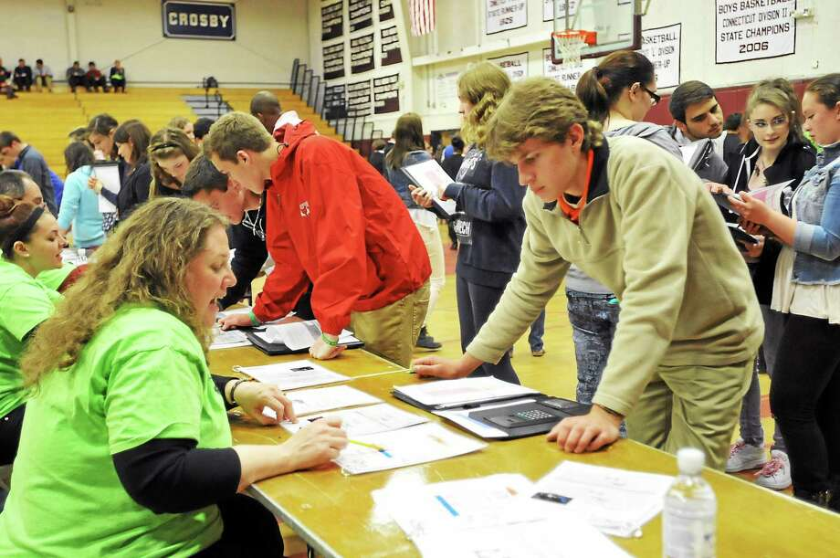 Wallace Michaud (Terryville High School) talks with Tammy Lamb about the cost of TV, phone & internet at the Torrington High School Financial Reality Fair Wednesday. Photo: Laurie Gaboardi — The Register Citizen
