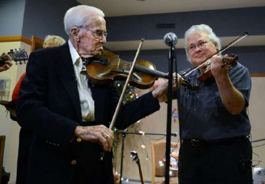 Lloyd Johnson, left, smiles as he plays a tune with renowned musician Peter Ostroushko, for Johnson's 100th birthday on Dec. 4, 2013.