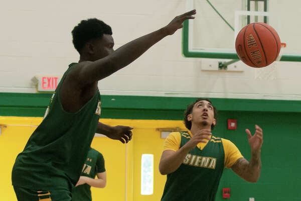 Freshman point guard Jordan Horn, right, receives a pass during a pre-season basketball practice on Saturday, Aug. 26, at Siena College in Albany. (Jenn March/Special to the Times Union)
