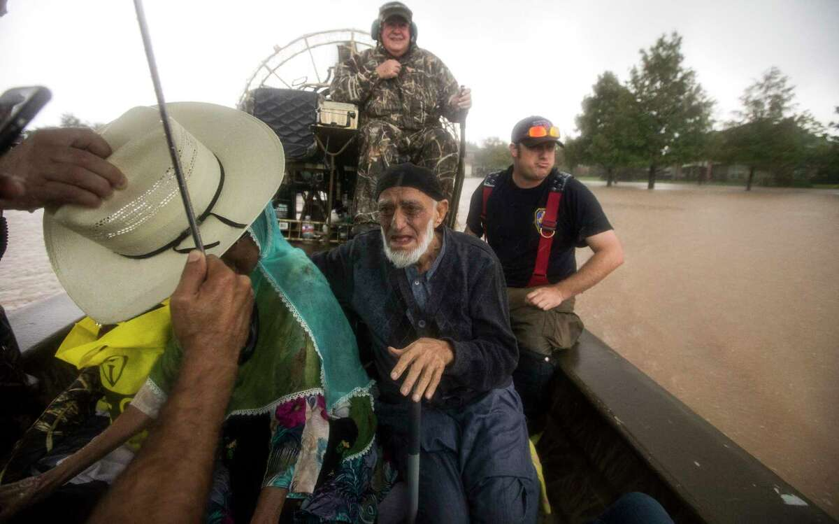 Tarmohamed Kara is evacuated with his wife, Mumtaz, from rising waters, from Tropical Storm Harvey, on an airboat in the Orchard Lakes subdivision on Sunday, Aug. 27, 2017, in unincorporated Fort Bend County, Texas.