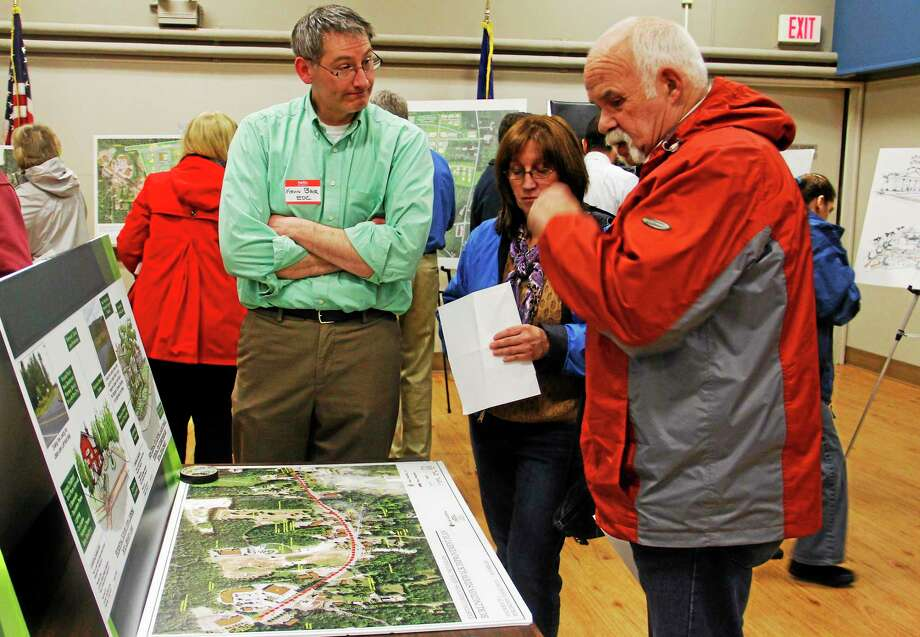 From left: Kevin Bair, Liz Draper and Don Provost, all of Burlington, discuss a schematic at the town's Village Center Plan Open House on Wednesday, April 30, 2014, in Burlington's Town Hall. More than 100 residents attended the open house despite rainy weather. Photo: Esteban L. Hernandez — Register Citizen