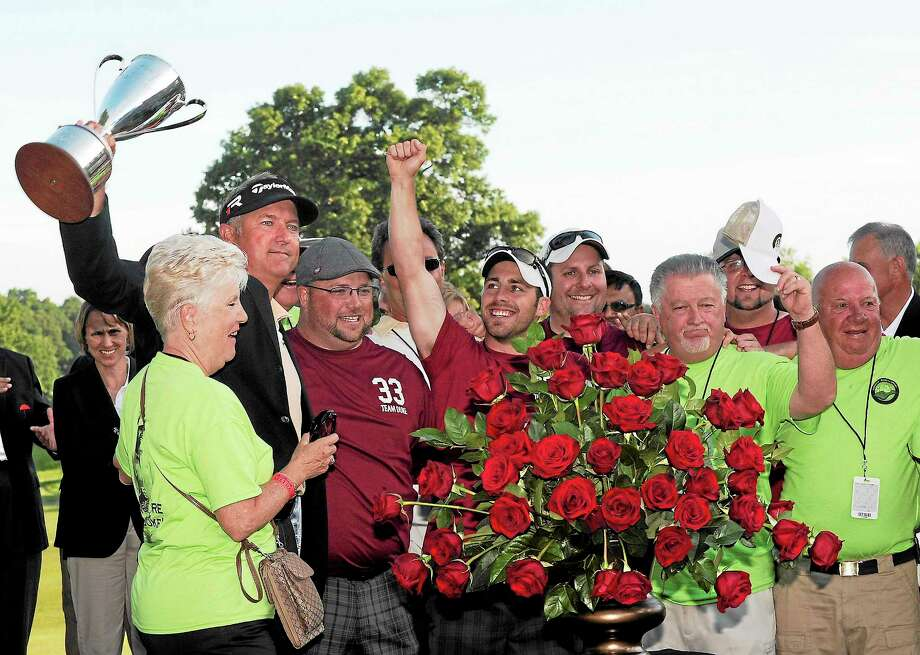Ken Duke raises the trophy with supporters after winning the Travelers Championship in Cromwell last June. Duke won the tournament with a birdie on the second playoff hole. Photo: Fred Beckham — The Associated Press  / FR153656 AP