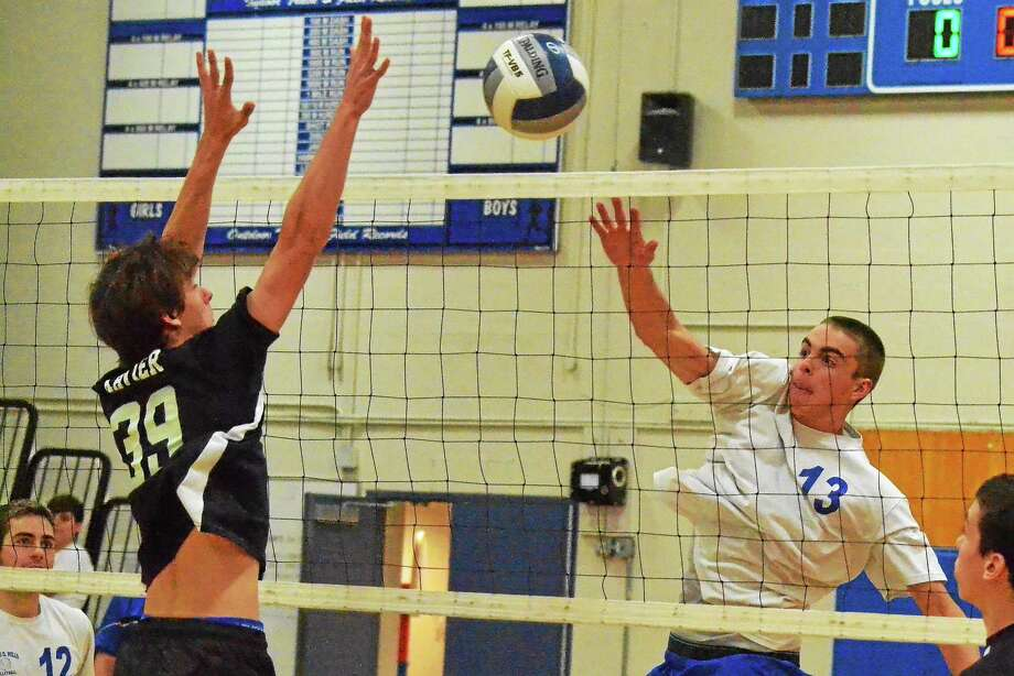 Lewis Mills' Alexander Daigle spikes the ball past Xavier's Ryan Garafalo, who attempts to block. Daigle finished with 14 kills in the Spartans 3-1 loss to Xavier. Photo: Pete Paguaga — Register Citizen