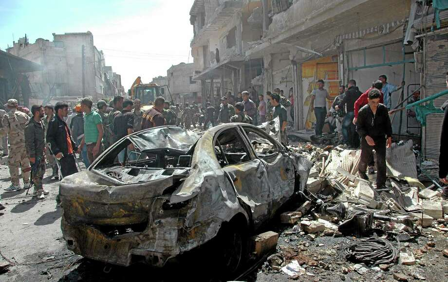 In this photo released by the Syrian official news agency SANA, Syrian people gather at the site of one of two car bombs that exploded in the pro-government district of Zahra in the central Syrian city of Homs, Syria, Tuesday, April 29, 2014. Dozens of people were killed and wounded in the attacks just hours after one of the deadliest mortar strikes in the heart of the capital, Damascus, killed 14, officials and state media said. (AP Photo/SANA) Photo: AP / SANA