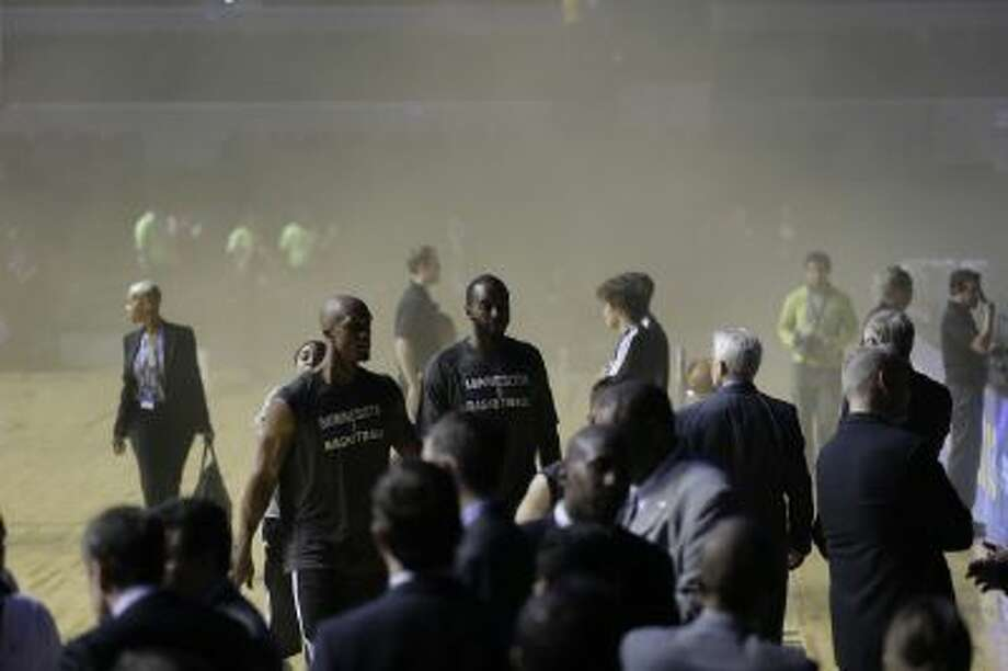 Players of the Minnesota Timberwolves leave as smoke engulfs the basketball court during a regular season NBA match between the Timberwolves and the San Antonio Spurs in Mexico City,