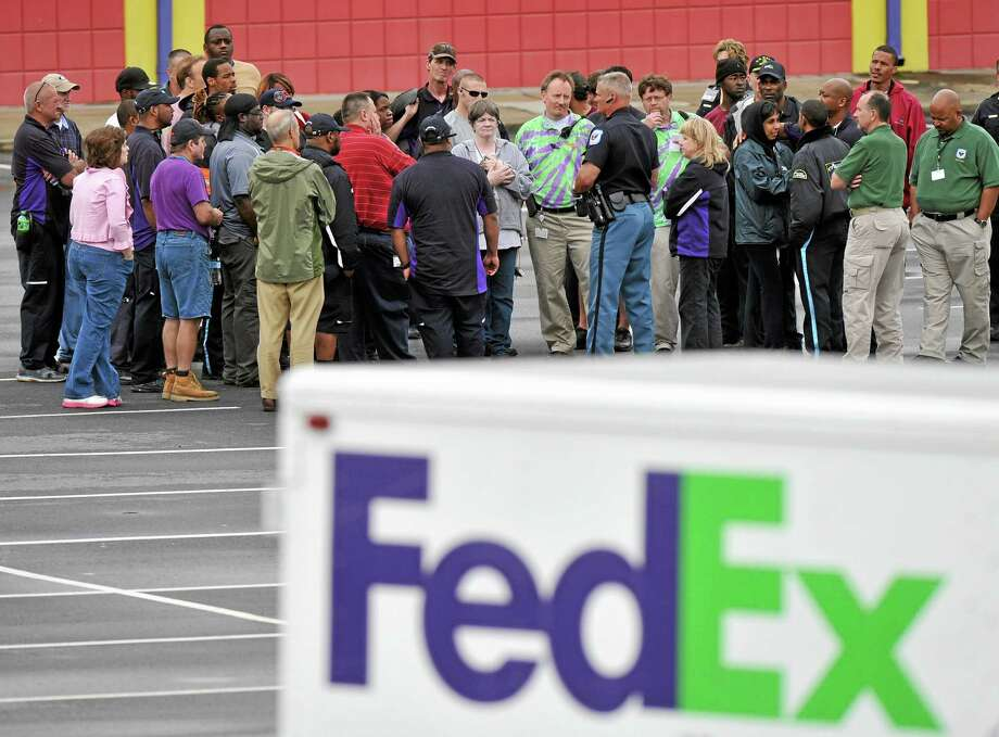 "A Cobb County Police Officer speaks to FedEx employees and family members gathered at the parking lot of a skating rink located near the shipping facility where a gunman open fire in Kennesaw, Ga., on Tuesday, April 29, 2014.  A shooter described as being armed with an assault rifle and having bullets strapped across his chest ""like Rambo"" opened fire Tuesday morning at a FedEx station outside Atlanta, wounding at least six people before police found the suspect dead from an apparent self-inflicted gunshot.  (AP Photo/Atlanta Journal-Constitution, Brant Sanderlin)  MARIETTA DAILY OUT; GWINNETT DAILY POST OUT; LOCAL TV OUT; WXIA-TV OUT; WGCL-TV OUT Photo: AP / AJC"