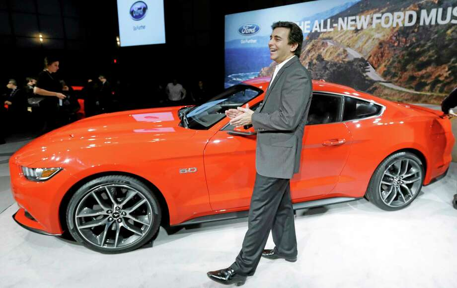 Mark Fields, left, chief operating officer for Ford Motor Company, stands next to the automaker's new 2015 Ford Mustang in Dearborn, Mich., Thursday, Dec. 5, 2013. The Mustang is celebrating its 50th birthday with a new design the automaker plans on taking global. It goes on sale next fall in North America and will arrive later in Europe and Asia. (AP Photo/Carlos Osorio) Photo: AP / AP