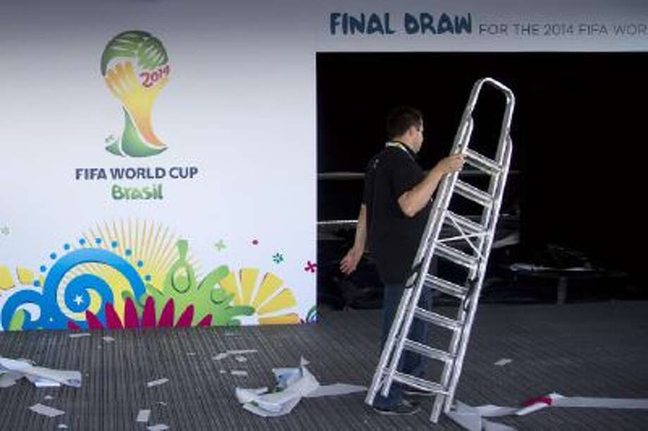 A worker carries a ladder outside the entrance of the large tent where the 2014 World Cup draw will take place in Costa do Sauipe, Brazil.