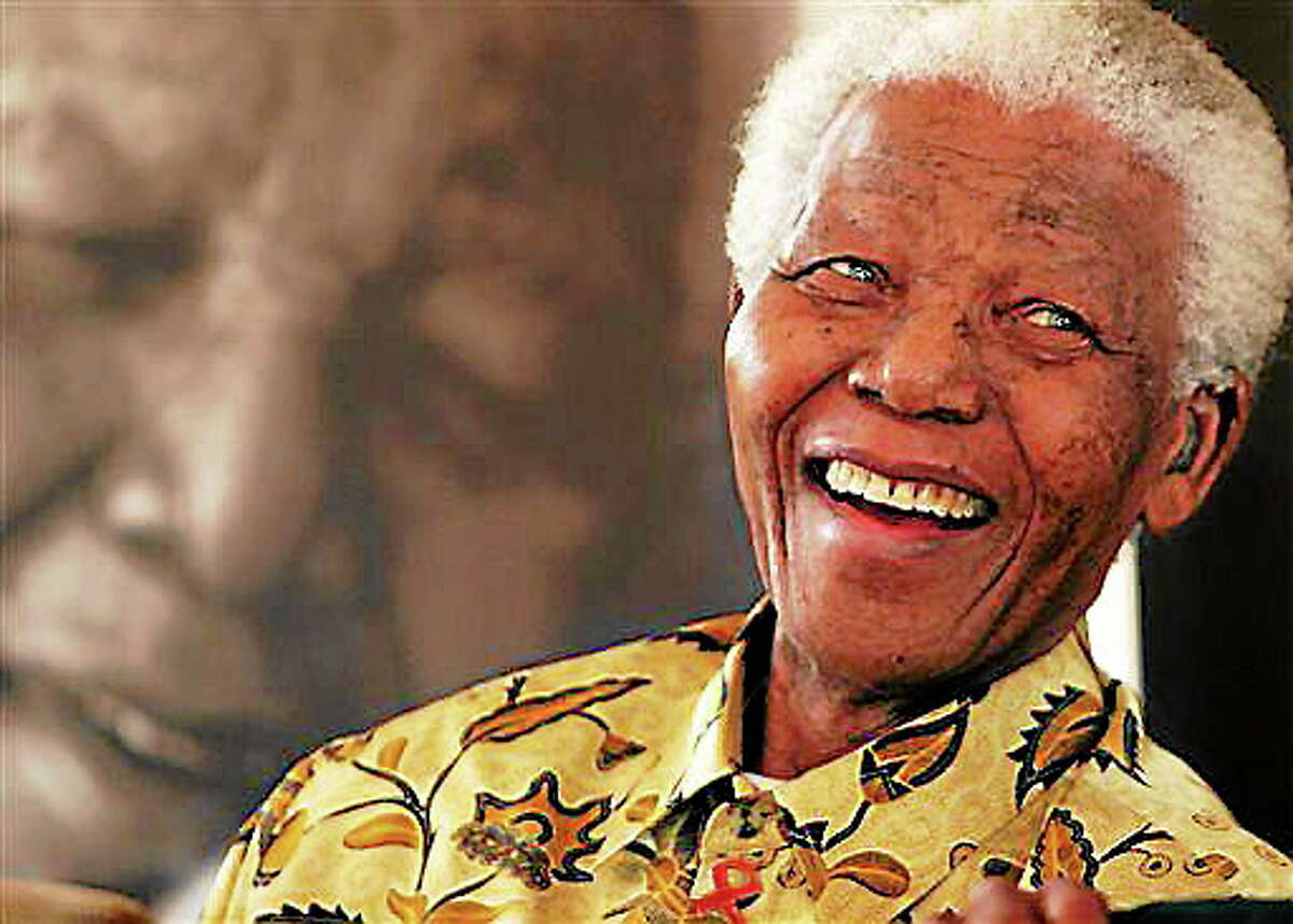 """FILE - In this Dec. 7, 2005, file photo, former South African President Nelson Mandela, 87, is in a jovial mood at the Mandela Foundation in Johannesburg, where he met with the winner and runner-up of the local """"Idols"""" competition. South Africa's president says, Thursday, Dec. 5, 2013, that Mandela has died. He was 95. (AP Photo/Denis Farrell, File)"""