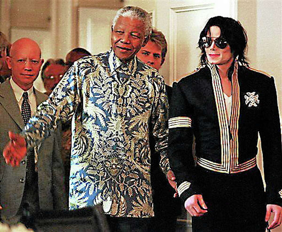 FILE - In this March 23, 1999 file photo, South African President Nelson Mandela, left, and American pop singer Michael Jackson arrive at a news conference in Cape Town, South Africa, where Jackson announced dates for two concerts with profits to go to various funds including the Nelson Mandela Children's Fund. South Africa's president Jacob Zuma says, Thursday, Dec. 5, 2013, that Mandela has died. He was 95. (AP Photo/Obed Zilwa, File)