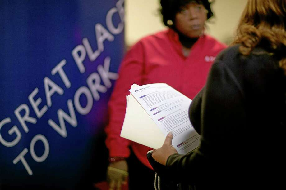 FILE - In this  Thursday, Nov. 14, 2013, file photo, Jimmetta Smith, of Lithonia, Ga., right, the wife of a U.S. Marine veteran, holds her resume while talking with Rhonda Knight, a senior recruiter for Delta airlines, at a job fair for veterans and family members at the VFW Post 2681, in Marietta, Ga. The Labor Department reports on the number of Americans who applied for unemployment benefits last week on Thursday, Nov. 21, 2013. (AP Photo/David Goldman, File) Photo: AP / AP