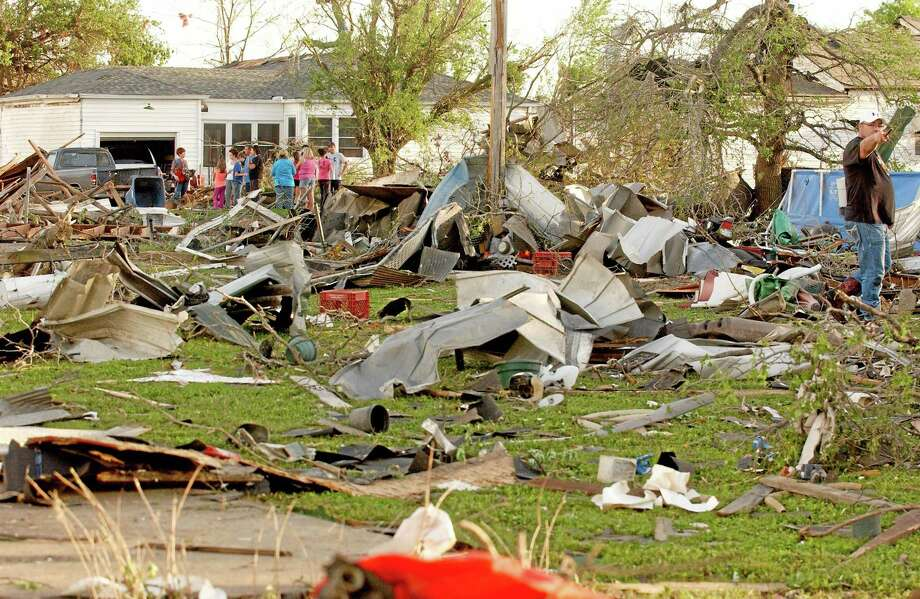 Quapaw, Okla. residents survey the damage in a residential neighborhood struck by a tornado on Sunday evening, April 27, 2014. A powerful storm system rumbled through the central and southern United States on Sunday, spawning a massive tornado that carved path of destruction through the northern Little Rock suburbs and another twister that killed two people in Oklahoma and injured others in Kansas. Photo: AP Photo/Tulsa World,  Gary Crow  / Gary Crow