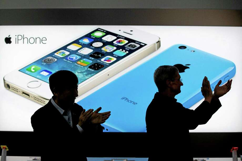 FILE - In this Jan. 17, 2014 file photo, Apple CEO Tim Cook, right, and China Mobile's chairman Xi Guohua are silhouetted against a screen showing iPhone products as they applaud during a promotional event that marks the opening day of sales of China Mobile's 4G iPhone 5s and iPhone 5c at a shop of the world's largest mobile phone operator in Beijing, China. The high-stakes battle between the world's largest smartphone makers is scheduled to wrap up this week after a monthlong trial that has pulled the curtain back on just how very cutthroat the competition is between Apple and Samsung. Closing arguments in the patent-infringement case are scheduled to begin Monday, April 28 with the two tech giants accusing each other, once again, of ripping off designs and features. At stake: $2 billion if Samsung loses, a few hundred million if Apple loses. (AP Photo/Alexander F. Yuan, File) Photo: AP / AP