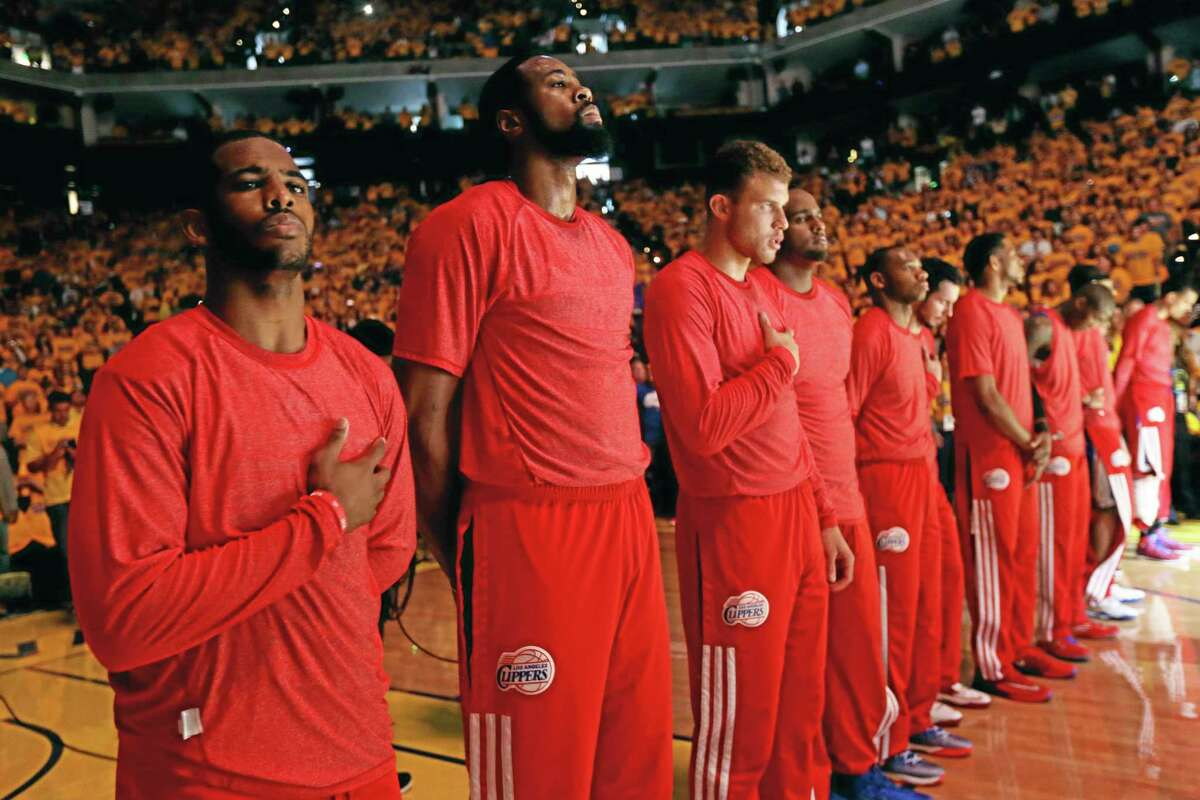 Members of the Los Angeles Clippers listen to the national anthem before Game 4 of an opening-round NBA basketball playoff series against the Golden State Warriors on Sunday, April 27, 2014, in Oakland, Calif. The Clippers chose not to speak publicly about owner Donald Sterling. Instead, they made a silent protest. The players wore their red Clippers' shirts inside out to hide the team's logo. (AP Photo/Marcio Jose Sanchez)
