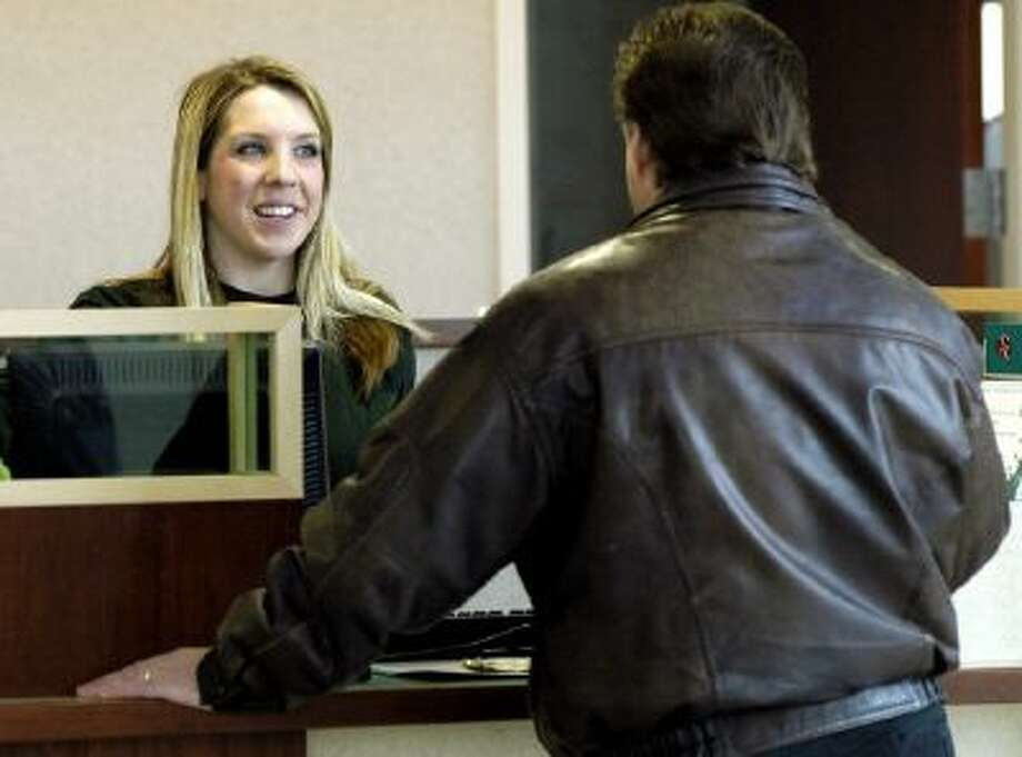 Beth Waters, left, a teller at the National City Bank branch in North Royalton, Ohio helps a customer, Friday, March 24, 2006.