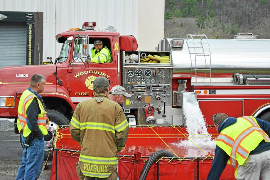 Firefighters from all over Litchfield and Fairfield Counties took part in a regional fire drill aimed to enhance cooperation between departments. Here tankers dump water from a nearby quarry into the holding area to use by other trucks to battle a fire. John Berry - The Register Citizen Photo: Journal Register Co.