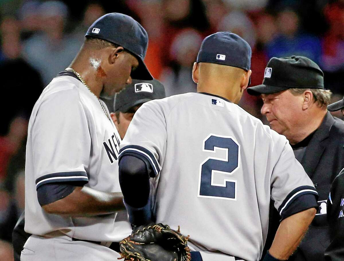 """Home plate umpire Gerry Davis, right, confers on the mound with New York Yankees starting pitcher Michael Pineda, left. While Pineda received a 10-game suspension for having pine tar on his neck, Register sports columnist Chip Malafronte was hoping for another patented Pineda excuse, such as, """"It's a birthmark."""""""