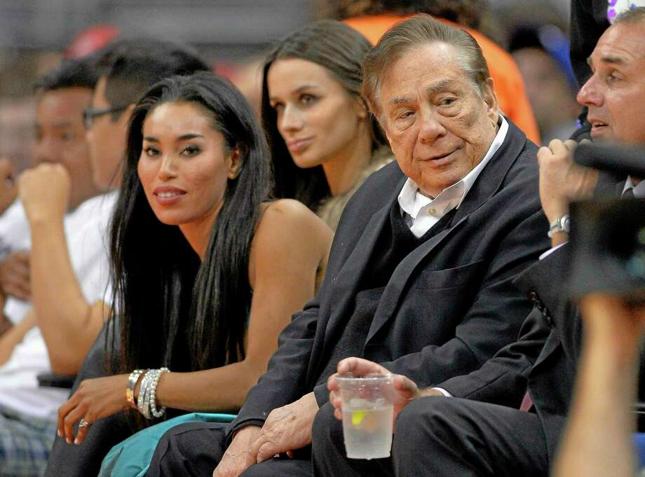 "In this Oct. 25, 2013 photo, Clippers owner Donald Sterling, right, and V. Stiviano, left, watch a game against the Sacramento Kings in Los Angeles. The NBA is investigating a report of an audio recording in which a man purported to be Sterling makes racist remarks while speaking to Stiviano. NBA spokesman Mike Bass said in a statement Saturday that the league is in the process of authenticating the validity of the recording posted on TMZ's website. Bass called the comments ""disturbing and offensive."" Photo: Mark J. Terrill — The Associated Press  / AP"