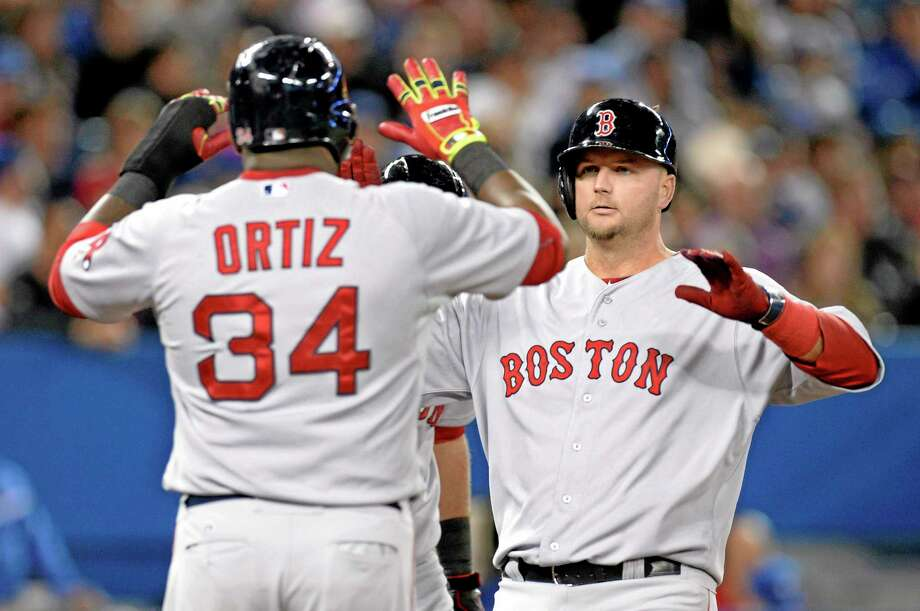 Boston Red Sox catcher A.J. Pierzynski is congratulated by David Ortiz after hitting a grand slam during the third inning of Saturday's win over the Blue Jays in Toronto. Photo: Frank Gunn — The Canadian Press  / CP