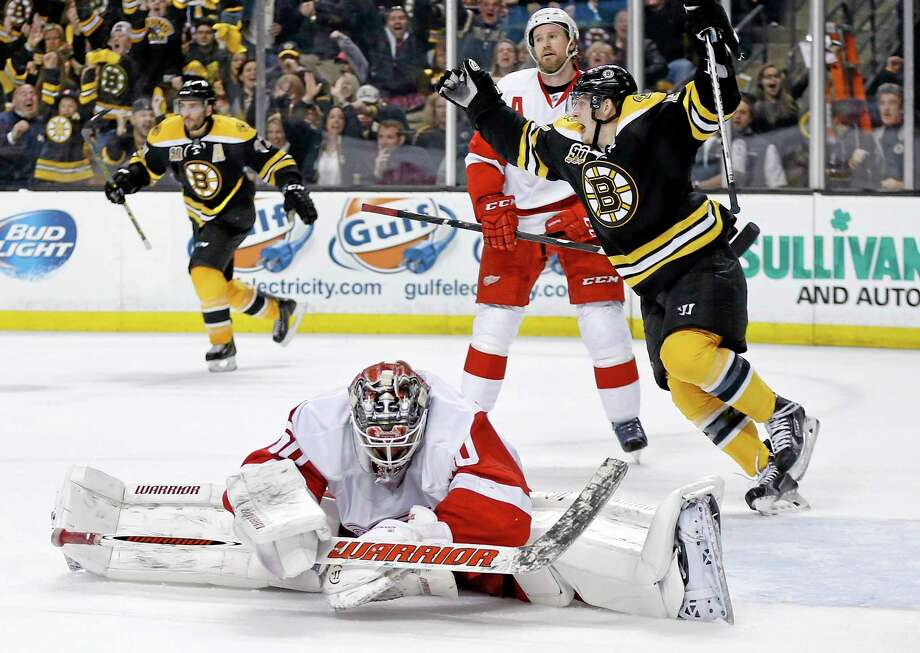 Detroit Red Wings goalie Jonas Gustavsson sprawls on the ice as the Bruins' Torey Krug, center, celebrates a goal by teammate Zdeno Chara during the second period of Game 5 on Saturday in Boston. Photo: Michael Dwyer — The Associated Press  / AP