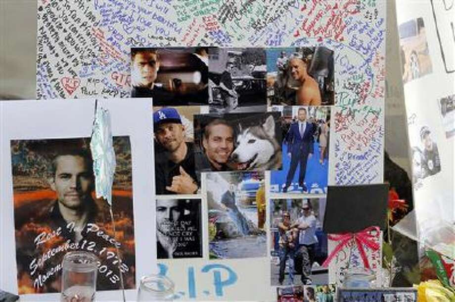 Photos and messages are seen at a roadside memorial at the site of the auto crash that took the life of actor Paul Walker and another man, in the small community of Valencia, Calif., Monday, Dec. 2, 2013. Photo: AP / AP