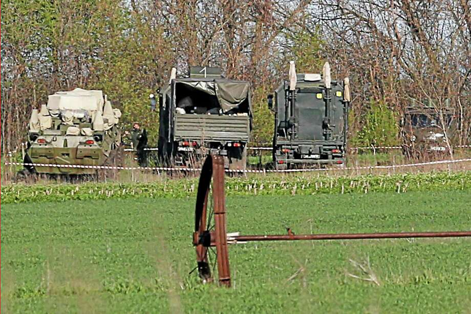 Russian army vehicles are parked about 2 kilometers (1,24 miles) from the Ukrainian border at Novoshakhtinsk, Rostov region, Russia, Saturday, April 26, 2014. (AP Photo/Pavel Golovkin) Photo: AP / AP