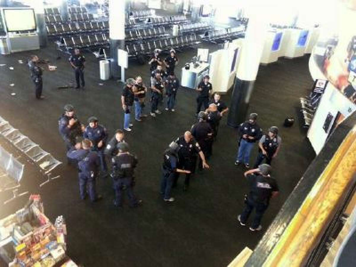 Police officers stand near an unidentified weapon in Los Angeles International Airport on Friday, Nov. 1, 2013 after a gunman opened fire in Terminal 3.