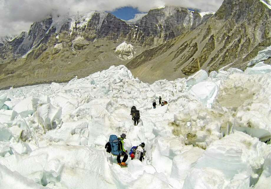 FILE - In this May 22 2013 file photo, climbers descend Khumbu Icefall on their way back to Base Camo after summitting the 8,850-meter (29,035-foot) Mount Everest. With its dreams of covering a daredevil's attempt to jump off Mount Everest over, the Discovery network is instead making a documentary on the avalanche, Friday, 18, 2014, that killed more than a dozen mountain guides. Discovery President Eileen O'Neill said Tuesday, April 22,  the network hopes to air the film within the next few weeks. Discovery will encourage viewers to donate to a relief fund for families of the Sherpa guides killed in the disaster. Several of the Sherpas killed were helping prepare for American Joby Ogwyn's planned jump from the summit in a wingsuit. Discovery planned to show the stunt on live television May 11.(AP Photo/ Pasang Geljen Sherpa, FIle) Photo: AP / AP