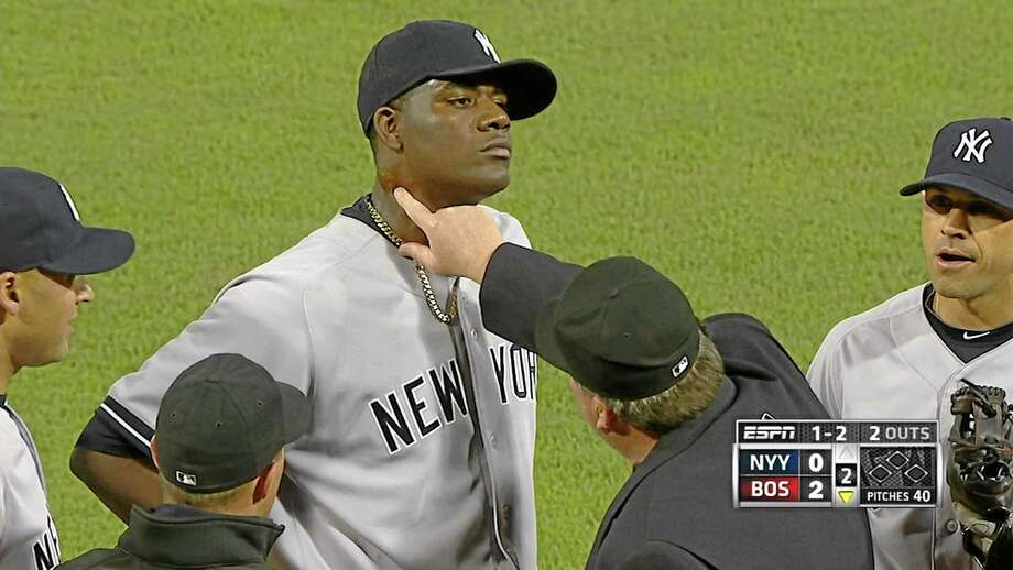 In this photo taken from video and provided by ESPN, home plate umpire Gerry Davis touches the neck of New York Yankees starting pitcher Michael Pineda in the second inning of Wednesday night's game against the Red Sox at Fenway Park in Boston. Pineda was ejected after umpires found pine tar on his neck. MLB suspended Pineda 10 games on Thursday. Photo: The Associated Press — ESPN  / ESPN