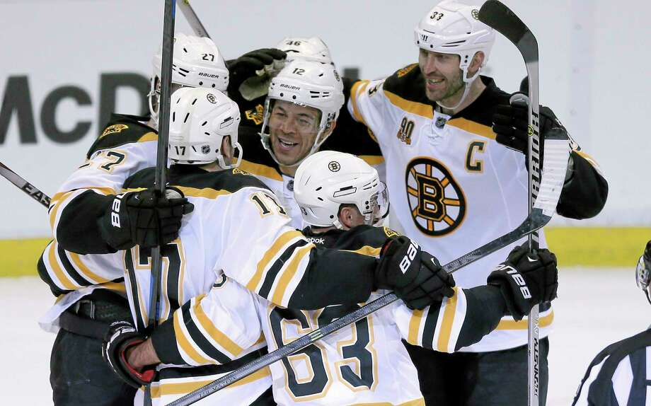 Boston Bruins right wing Jarome Iginla, center, is mobbed by teammates as they celebrate their 3-2 overtime win in Game 4 against the Detroit Red Wings Thursday. Photo: Carlos Osorio — The Associated Press  / AP